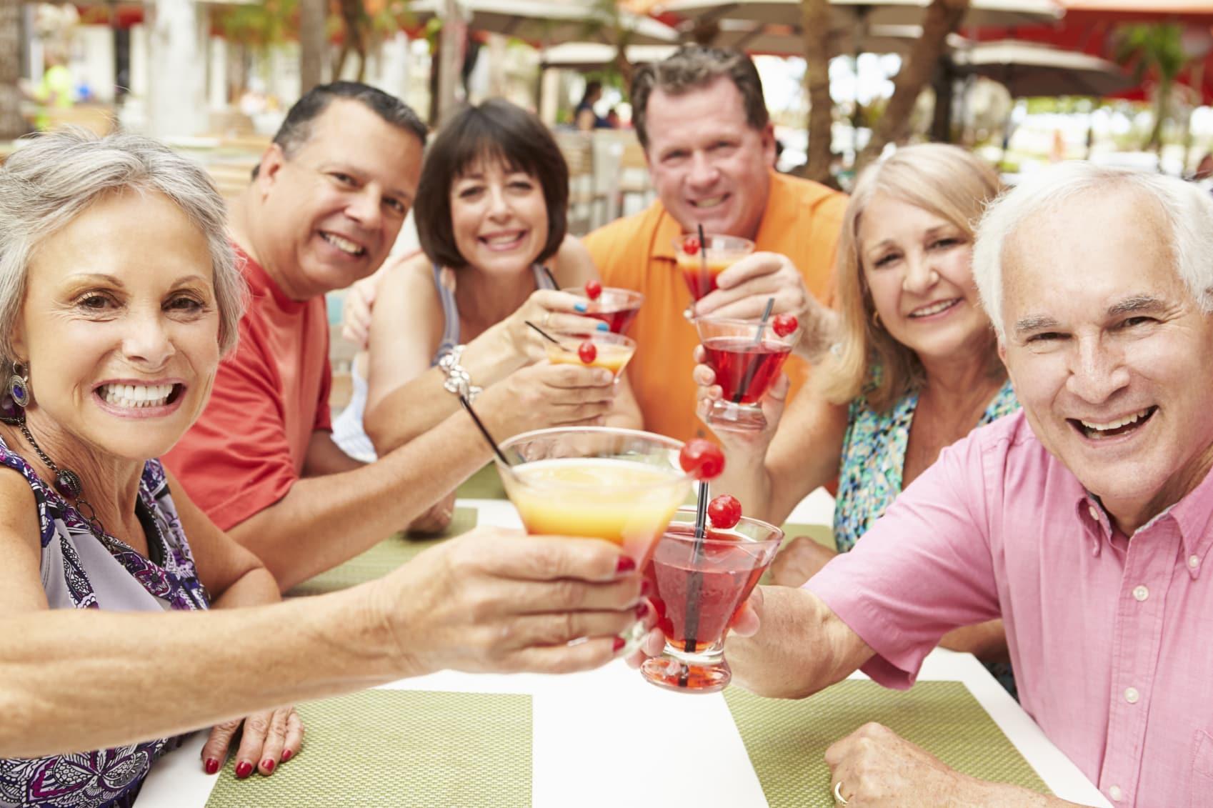 Group Of Senior Friends Enjoying Cocktails In Bar Together