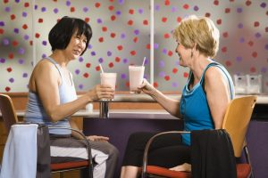 Mature Asian and Caucasian adult females sitting at table in health club cafeteria.