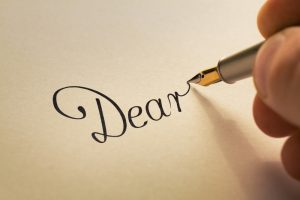 amintro Hand is writing calligraphic letter starting with dear using old pen on yellow paper