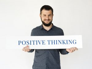 man holding a sign that says positive thinking